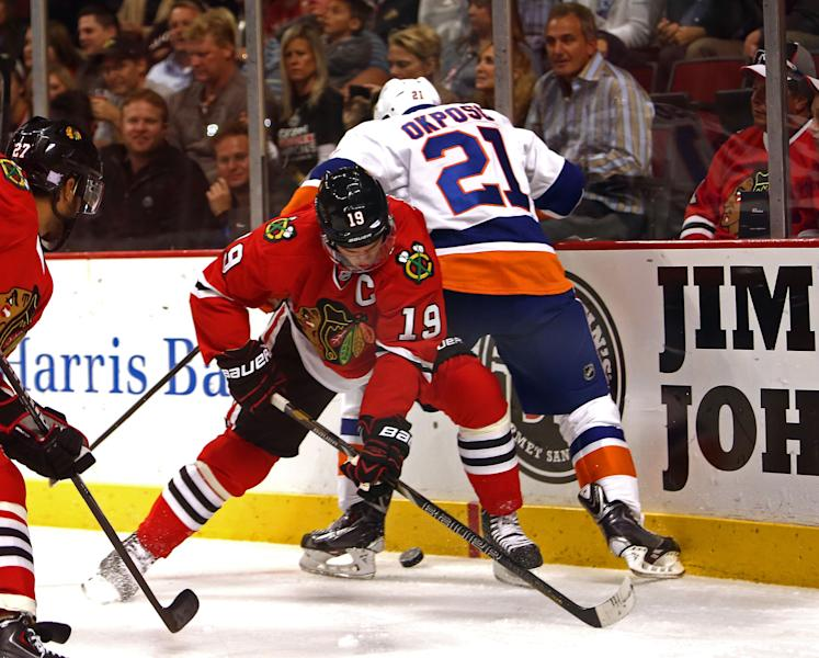 Chicago Blackhawks' Jonathan Toews tries to get the puck from under New York Islanders' Kyle Okposo during the first period of an NHL hockey game in Chicago on Friday, Oct. 11, 2013. (AP Photo/Charles Cherney)