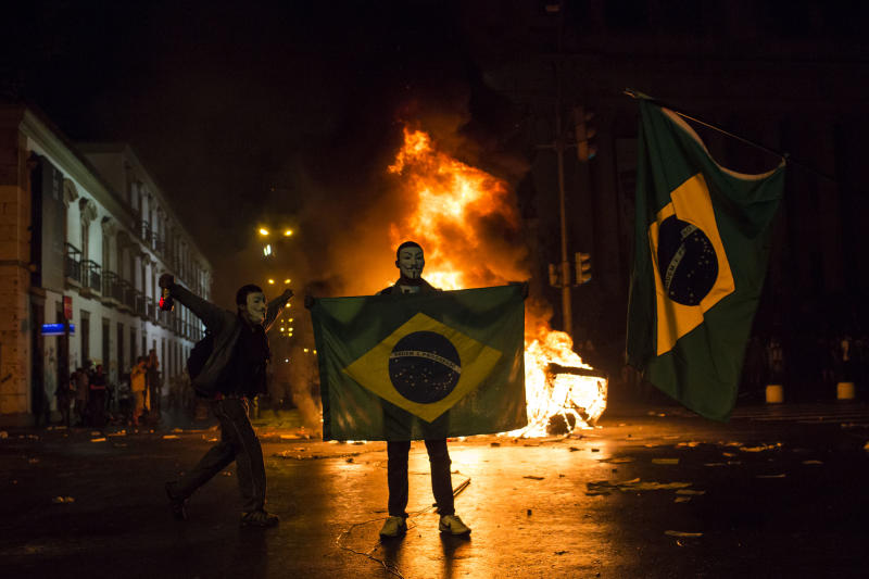 A demonstrator holds a Brazilian flag in front of a burning barricade during a protest in Rio de Janeiro in Rio de Janeiro, Brazil, Monday, June 17, 2013. Protesters massed in at least seven Brazilian cities Monday for another round of demonstrations voicing disgruntlement about life in the country, raising questions about security during big events like the current Confederations Cup and a papal visit next month. (AP Photo/Felipe Dana)