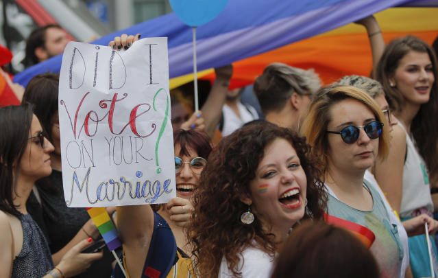 "<p>Participants, one holding a banner that reads ""Did I vote on your marriage?"" react, during a gay pride parade in Bucharest, Romania, Saturday, June 9, 2018. People taking part in the gay pride parade in the Romanian capital demanded more rights and acceptance for same-sex couples. (Photo: Vadim Ghirda/AP) </p>"