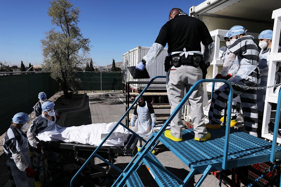Inmates load bodies into a refrigerated temporary morgue.
