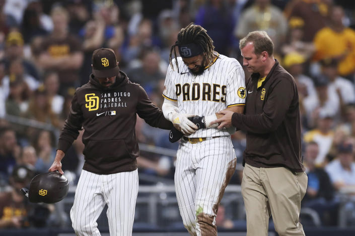 San Diego Padres' Fernando Tatis Jr., center, is helped off the field by manager Jayce Tingler, left, and a trainer during the first inning of the team's baseball game against the Colorado Rockies, Friday, July 30, 2021, in San Diego. (AP Photo/Derrick Tuskan)