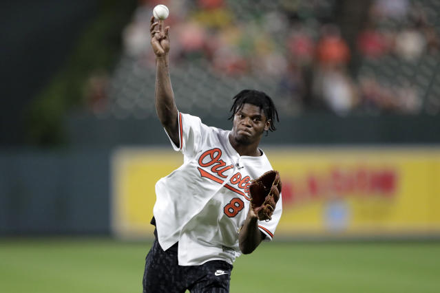 Baltimore Ravens NFL football quarterback Lamar Jackson throws a ceremonial first pitch prior to a baseball game between the Baltimore Orioles and the Washington Nationals, Wednesday, July 17, 2019, in Baltimore. (AP Photo/Julio Cortez)