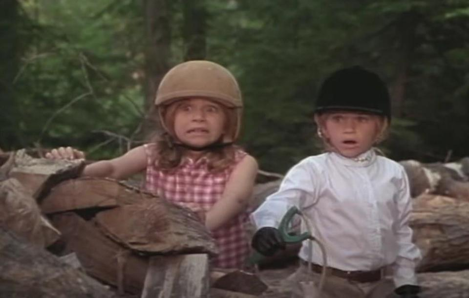 Alyssa and Amanda wear riding clothes and look horrified while standing behind stacks of chooped wood