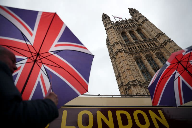 People carrying British Union Jack flag themed umbrellas walk past the Houses of Parliament in London