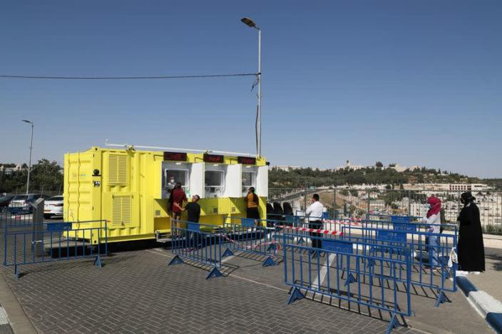 People stand in a queue as they wait to get tested for the coronavirus disease (COVID-19) in East Jerusalem