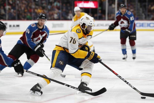 Nashville Predators defenseman P.K. Subban picks up the puck as Colorado Avalanche defenseman Tyson Barrie, front left, and left wing Blake Comeau defend during the second period of an NHL hockey game Friday, March 16, 2018, in Denver. (AP Photo/David Zalubowski)