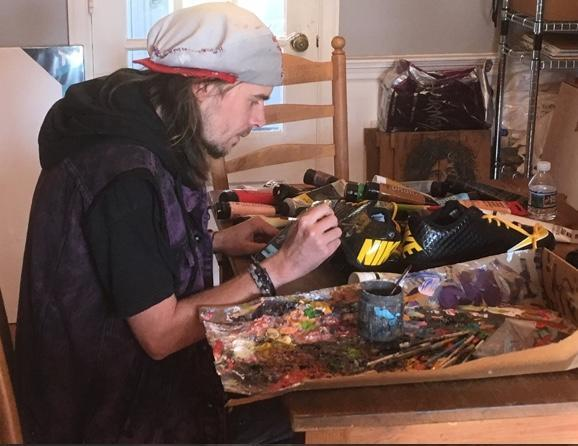 Artist Corey Pane gets to work on a pair of cleats. (Photo courtesy of Corey Pane)