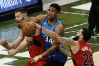 Milwaukee Bucks' Giannis Antetokounmpo goes after a loose ball with Toronto Raptors' Aron Baynes qnd Fred VanVleet (23) during the second half of an NBA basketball game Thursday, Feb. 18, 2021, in Milwaukee. (AP Photo/Morry Gash)