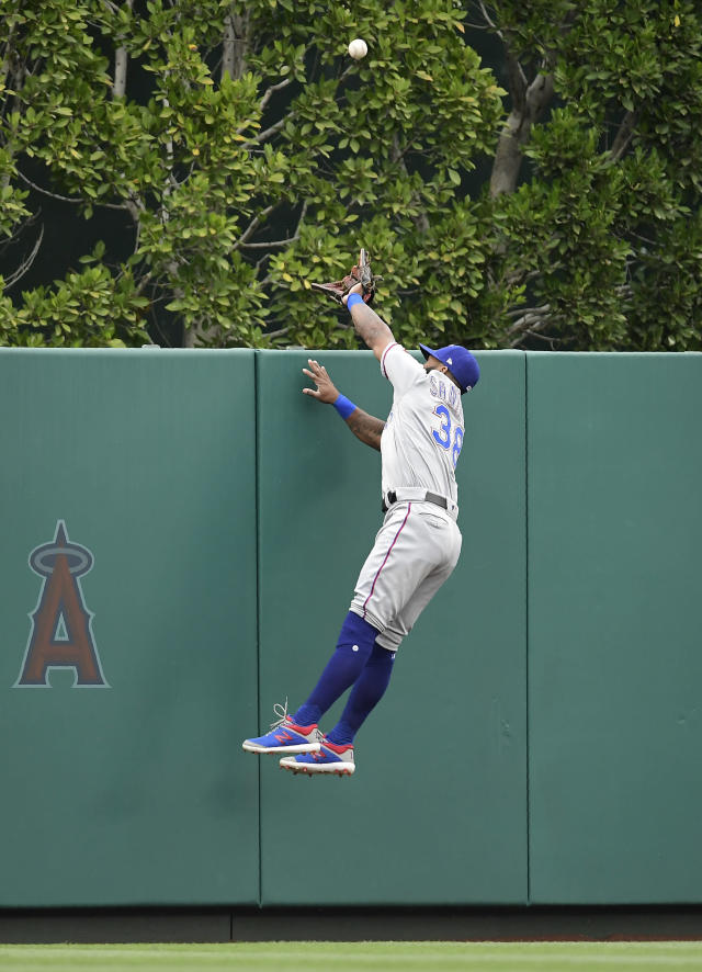 Texas Rangers center fielder Danny Santana cannot reach a ball hit by Los Angeles Angels' Mike Trout for a solo home run during the first inning of a baseball game Sunday, May 26, 2019, in Anaheim, Calif. (AP Photo/Mark J. Terrill)