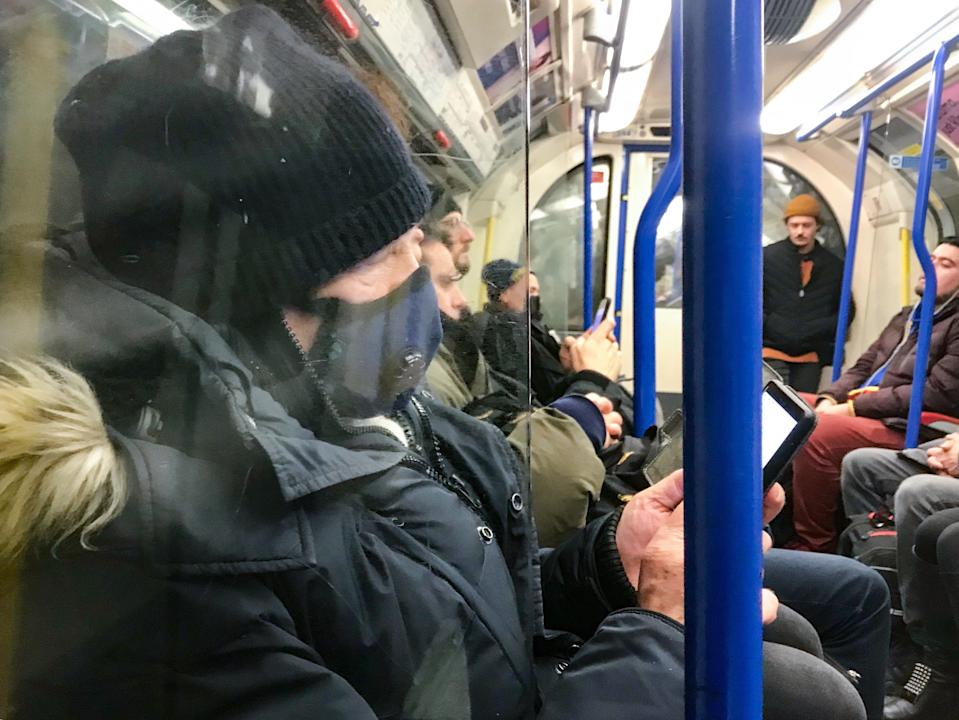 """A man wears a mask on the Piccadilly Line on the Underground, London. Prime Minister Boris Johnson has said it is """"highly likely"""" the UK will see a growing number of coronavirus cases, but stressed that """"for the vast majority of people in this country we should be going about our business as usual""""."""