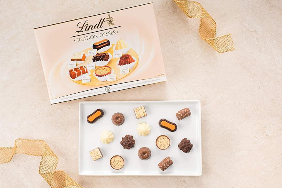 Box of Lindt Creation Dessert Gift Box with chocolates displayed on a white tray.