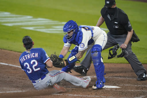 Seattle Mariners catcher Joseph Odom tags out Texas Rangers' Derek Dietrich as home plate umpire Lance Barrett looks on during the seventh inning of a baseball game, Sunday, Sept. 6, 2020, in Seattle. Dietrich was trying to score on a double hit by Leody Taveras. (AP Photo/Ted S. Warren)