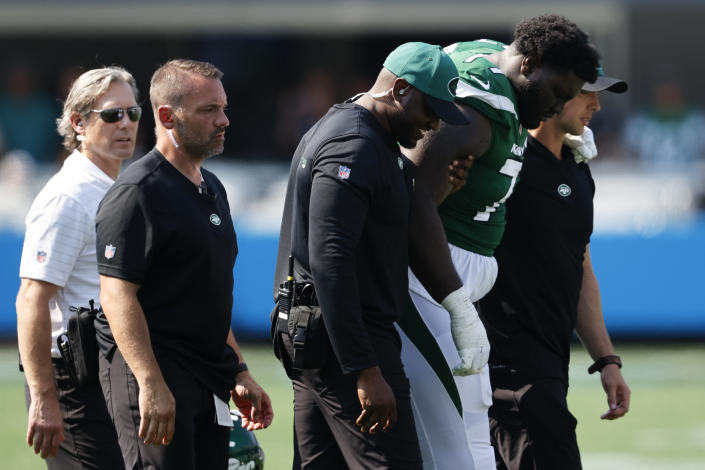 New York Jets offensive tackle Mekhi Becton is helped off the field during the second half of an NFL football game against the Carolina Panthers Sunday, Sept. 12, 2021, in Charlotte, N.C. (AP Photo/Nell Redmond)