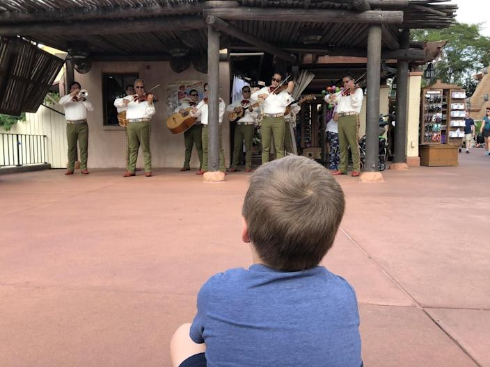 child sitting watching a performance in epcot world showcase at disney world