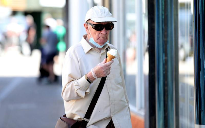 A man wearing a protective face mask and gloves eats an ice cream in Loughborough - PETER CZIBORRA/REUTERS