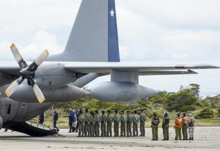 Military personnel stand by an Air Force plane before the unloading of human remains found during the search for the Chilean C-130 Hercules transport aircraft which crashed in the sea on its way to Antarctica