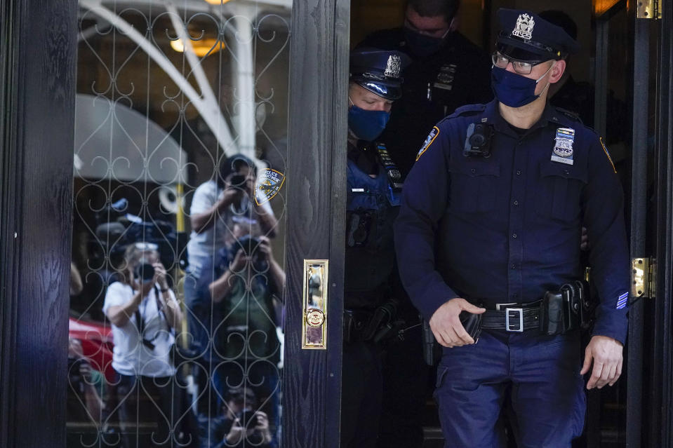 FILE - In this Wednesday, April 28, 2021, file photo, members of the media are reflected in the window of a door as New York City Police officers walk out of the apartment building where former New York Mayor Rudy Giuliani resides, in New York. Giuliani and his lawyers will get to designate which materials seized from him will be reviewed by a court-appointed expert reviewer to determine what should never be seen by federal prosecutors. As part of the investigation, federal agents seized 18 electronic devices from Giuliani's residence and his firm, Giuliani Partners LLC. (AP Photo/Mary Altaffer, File)