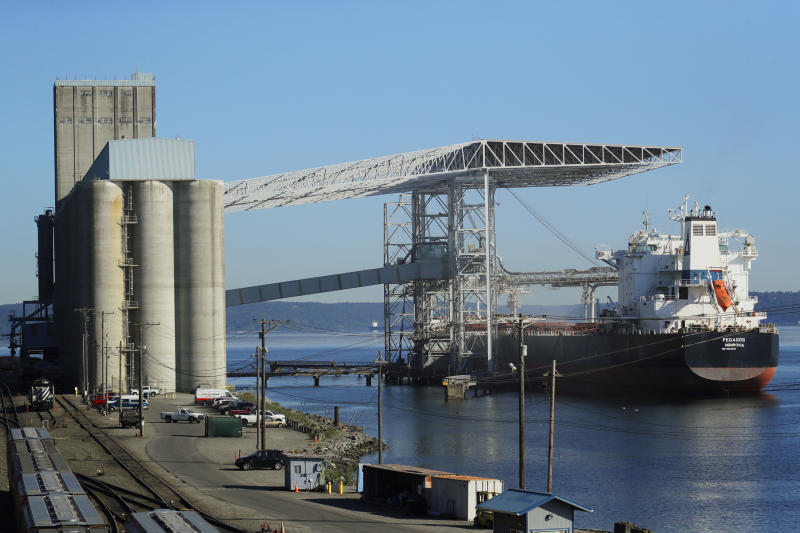 FILE - In this May 10, 2019, file photo a bulk carrier ship is loaded at the Temco grain terminal at the Port of Tacoma in Tacoma, Wash. Yields on 2-year and 10-year Treasury notes inverted early Wednesday, Aug. 14, a market phenomenon that shows investors want more in return for short-term government bonds than they do for long-term bonds. Longer-term yields have been falling due to anxiety that President Donald Trump's trade war could derail the global economy. (AP Photo/Ted S. Warren, File)