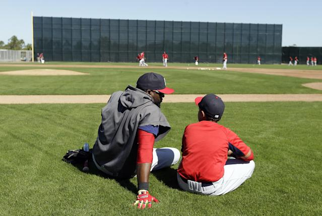 Boston Red Sox designated hitter David Ortiz, left, sits on the field with his son D'Angelo, right, during spring training baseball practice Tuesday, Feb. 18, 2014, in Fort Myers, Fla. (AP Photo/Steven Senne)