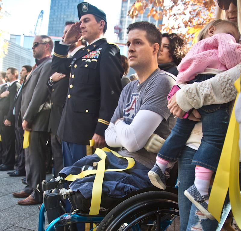 "FILE--In this Nov. 10, 2014, file photo, former U.S. Air Force Senior Airman Brian Kolfage, center, sits in a wheelchair next to his wife Ashley, right, who holds their daughter Paris, during the National September 11 Memorial and Museum's ""Salute to Service"" tribute honoring U.S. veterans in New York. Kolfage, a triple-amputee who lost his limbs serving in Iraq in the U.S. Air Force, started a GoFundMe page to help fund construction of President Donald Trump's border wall has already raised millions of dollars."