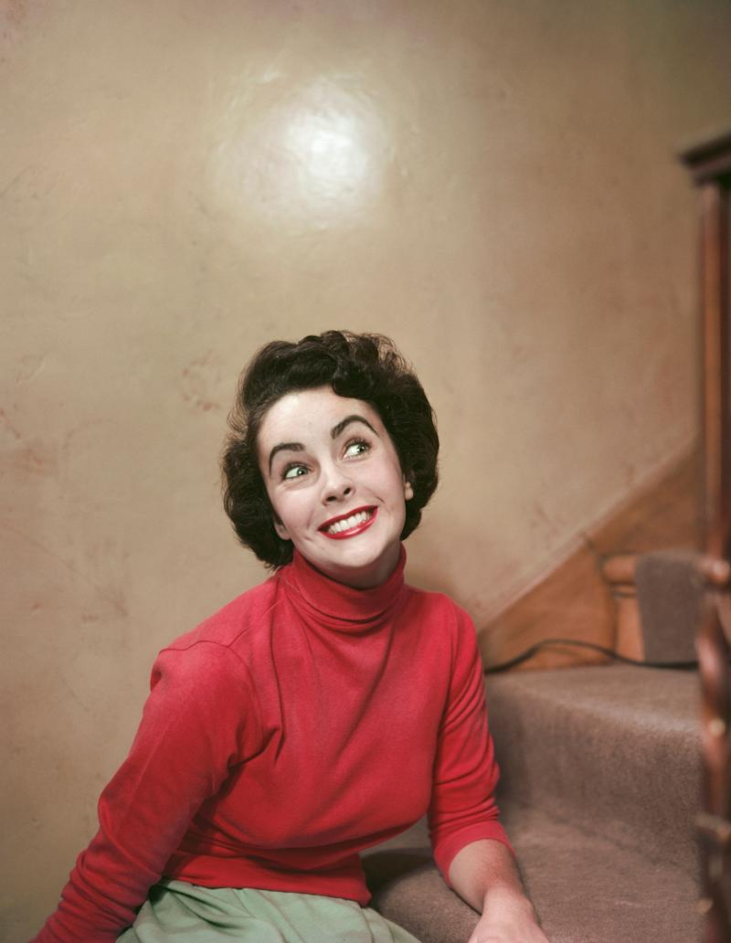 The actress offers a big smile on a stairway in a red turtleneck, sometime in the '50s.
