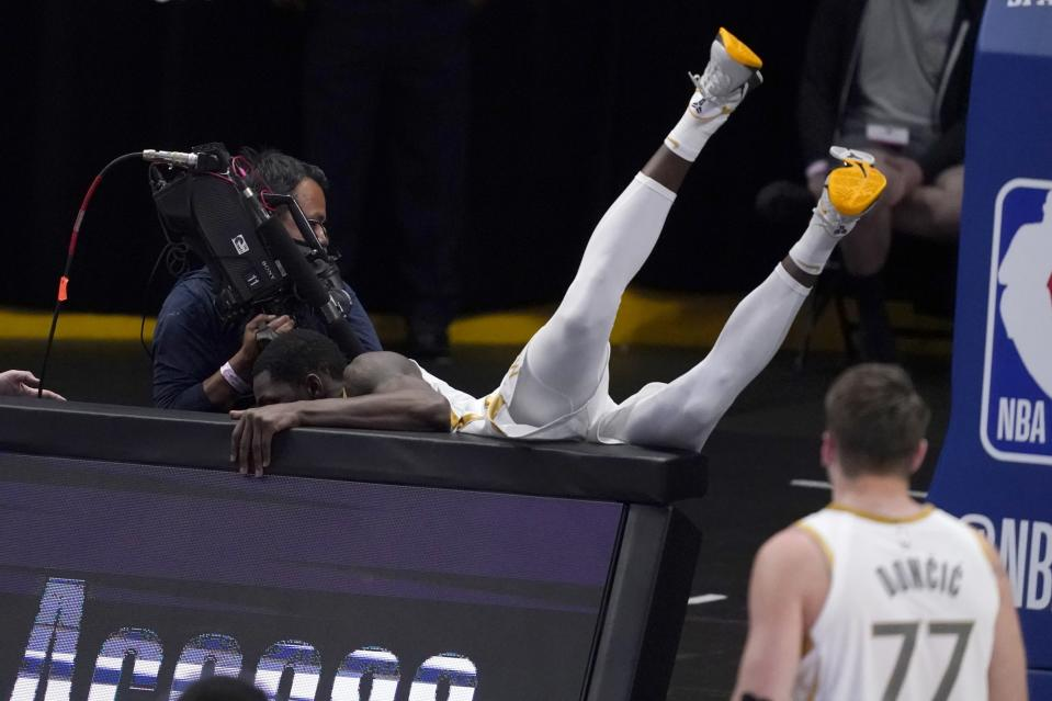 A camera operator moves away as Dallas Mavericks' Dorian Finney-Smith, falls over signage near base court during play as guard Luka Doncic (77) looks on in the second half of an NBA basketball game against the Brooklyn Nets in Dallas, Thursday, May 6, 2021. (AP Photo/Tony Gutierrez)