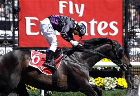 Jockey Damien Oliver crosses the finish line riding race favourite Fiorente to win the A$6 million ($5.7 million) Melbourne Cup at Flemington Racecourse in Melbourne
