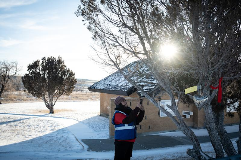 A member of the Northern Cheyenne rescue team photographs a gift brought in by Selena Not Afraid's neighbors at the rest stop where she was last seen near Hardin, Mont., Jan. 11, 2020. (Cristina Baussan/The New York Times)