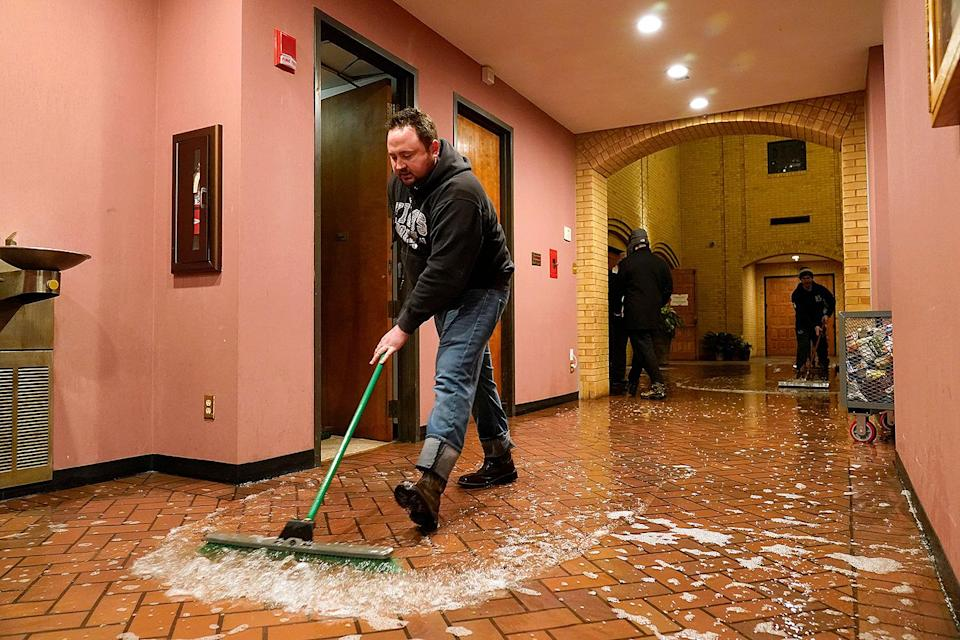<p>Father John Szatkowski of St. Paul The Apostle Church in Richardson, Texas, pushes water from a broken water line on Feb. 17. Many in the area are still without water or dealing with burst pipes due to the cold.</p>