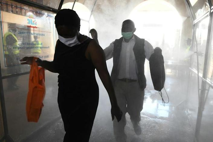 In Nairobi, public transport is operational, but passengers walk through a disinfectant tunnel as they prepare to board a commuter train at the main railway station before curfew (AFP Photo/SIMON MAINA)