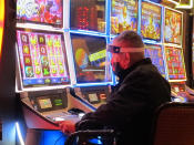 In this July 2, 2020 photo, a man plays a slot machine at the Golden Nugget casino in Atlantic City N.J. Gambling companies in the U.S. are increasingly bringing different forms of gambling together, including sports betting, casino gambling, internet gambling and daily fantasy sports, and partnering with media companies as they seek to increase revenue. (AP Photo/Wayne Parry)