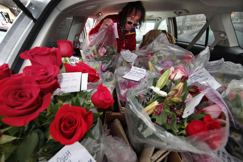 FILE - This Feb. 14, 2012 file photo shows a flower delivery driver loading his car with Valentine's Day deliveries in Pittsburgh. As Valentine's Day approaches, a new poll suggests Cupid's arrow hit the target for most Americans. The Associated Press-WE tv survey finds 66 percent of paired-off adults feel their relationships are perfect or nearly so, and just 3 percent think their partnerships have serious problems. All told, 68 percent of Americans are in committed relationships of some kind, and another 11 percent aren't currently coupled, but would like to be. Seventeen percent say they aren't seeking a relationship. (AP Photo/Gene J. Puskar, File)
