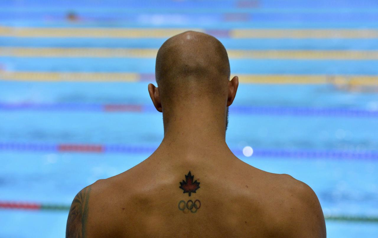 A tattoo of a maple leaf and the Olympic rings is seen on the back of Canada's Brent Hayden as he attends a training session at the main pool of the Aquatics Centre before the start of the London 2012 Olympic Games in London July 25, 2012.  REUTERS/Toby Melville (BRITAIN  - Tags: SPORT OLYMPICS SPORT SWIMMING)