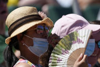 A spectator uses a fan to cool off at the U.S. Olympic Track and Field Trials Friday, June 25, 2021, in Eugene, Ore. (AP Photo/Ashley Landis)