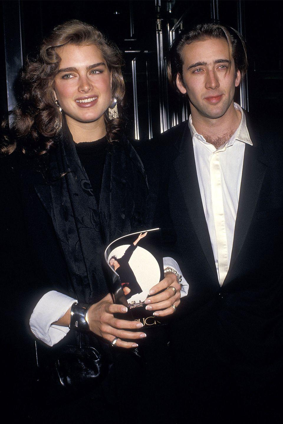 """<p>The model-slash-actress was rumored to be dating Nicolas Cage in 1987 when she was photographed attending the premiere of Cage's breakout film, <em>Moonstruck</em>. People believed their <a href=""""http://www.complex.com/pop-culture/2012/02/nicolas-cages-10-hottest-hook-ups/9"""" rel=""""nofollow noopener"""" target=""""_blank"""" data-ylk=""""slk:relationship was more serious off the red carpet"""" class=""""link rapid-noclick-resp"""">relationship was more serious off the red carpet</a>, but were confused as to how Shields could have gone from dating <a href=""""http://www.zimbio.com/John+F.+Kennedy+Jr.+Dating+History/articles/-iamQiWr8xD/John+F+Kennedy+Jr+dated+Brooke+Shields"""" rel=""""nofollow noopener"""" target=""""_blank"""" data-ylk=""""slk:JFK, Jr."""" class=""""link rapid-noclick-resp"""">JFK, Jr.</a> to Cage. </p>"""