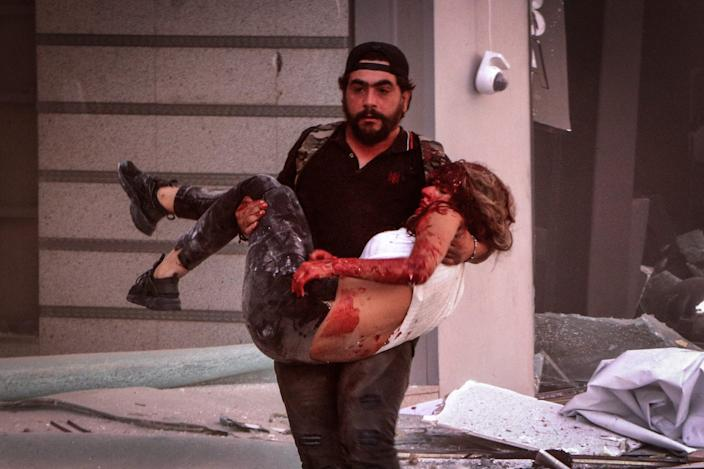 A man carries an injured person following a massive explosion in Beirut's port.
