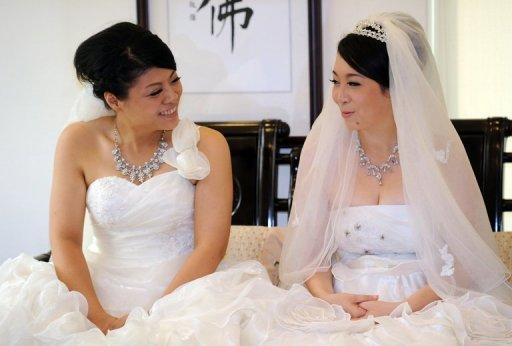 Taiwanese women Fish Huang (left) and her partner You Ya-ting smile during their same-sex Buddhist wedding ceremony in Taoyuan. The two women tied the knot in Taiwan's first same-sex Buddhist wedding, a move rights groups hope will help make the island the first society in Asia to legalise gay marriage