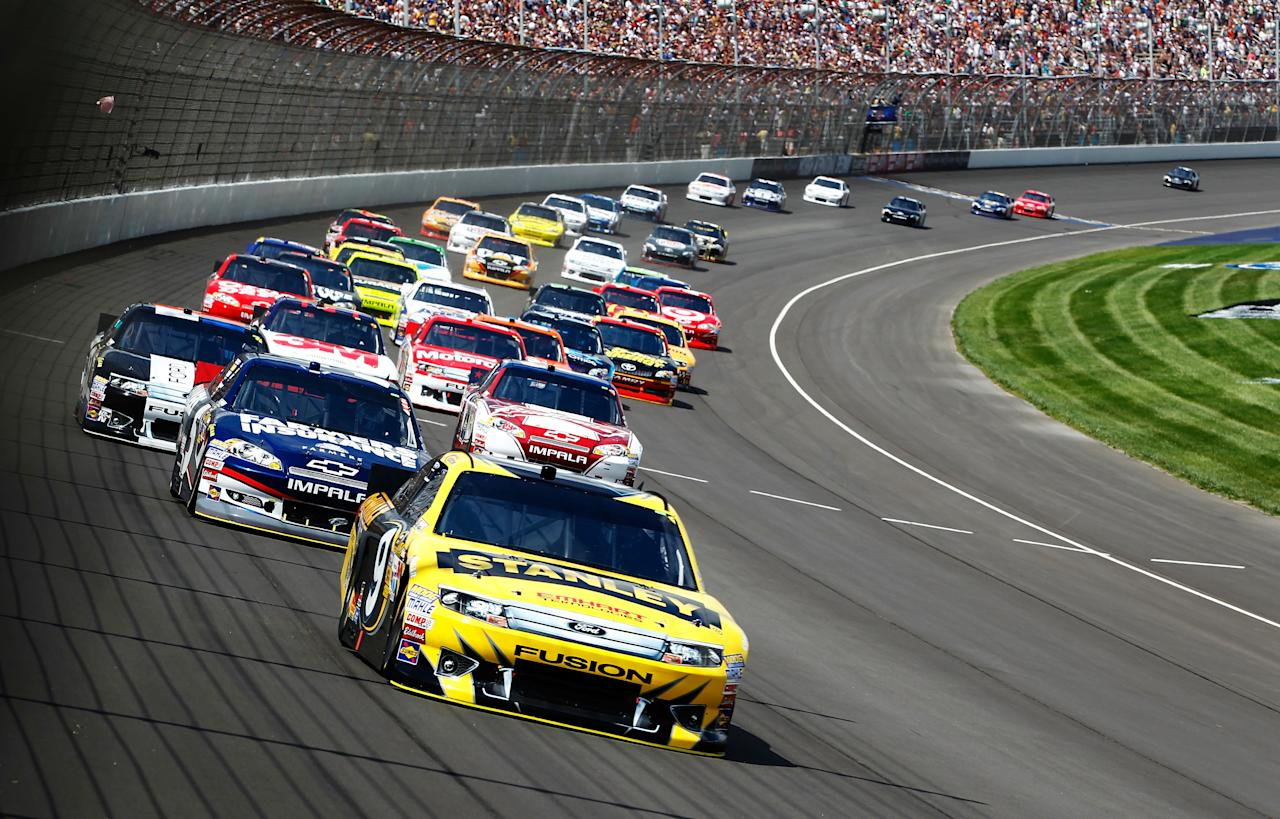 BROOKLYN, MI - JUNE 17:  Marcos Ambrose, driver of the #9 Stanley Ford, leads the field in the NASCAR Sprint Cup Series Quicken Loans 400 at Michigan International Speedway on June 17, 2012 in Brooklyn, Michigan.  (Photo by Jeff Zelevansky/Getty Images)