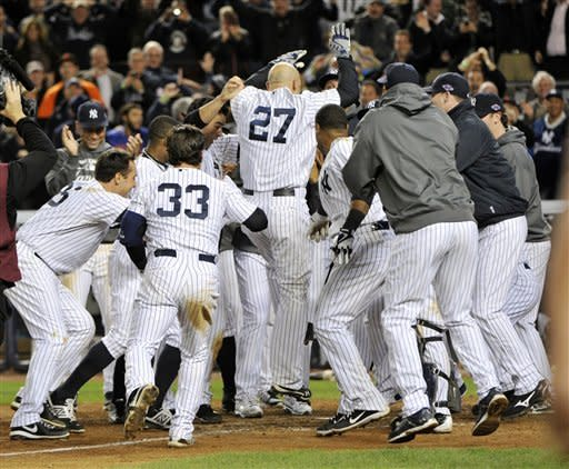 New York Yankees' Raul Ibanez (27) celebrates with teammates as he reaches home plate after hitting the game-winning home run during the 12th inning of Game 3 of the American League division baseball series against the Baltimore Orioles on Wednesday, Oct. 10, 2012, in New York. The Yankees won 3-2. (AP Photo/Bill Kostroun)