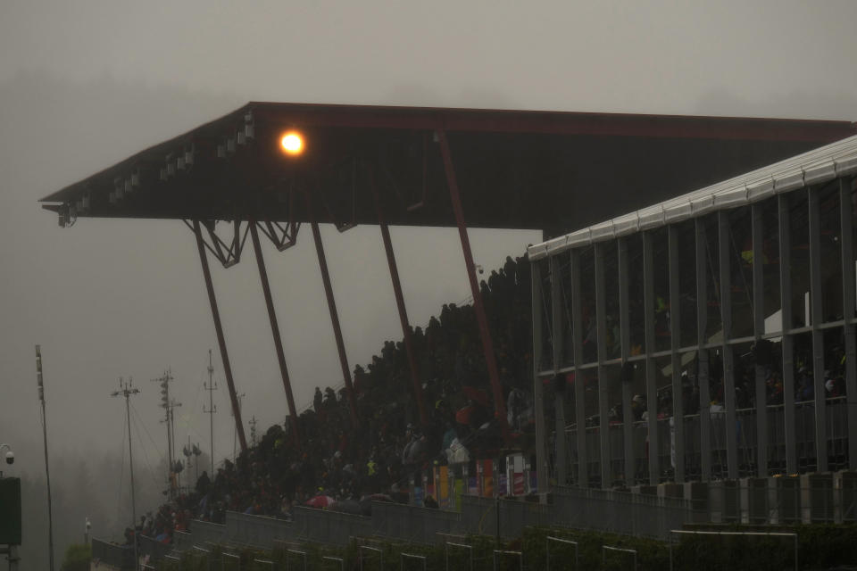 Spectators wait under an overhang during a rain delay at the Formula One Grand Prix at the Spa-Francorchamps racetrack in Spa, Belgium, Sunday, Aug. 29, 2021. (AP Photo/Francisco Seco)