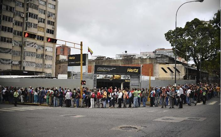 People wait in line to board a bus in Caracas, Venezuela on March 14, 2019 (AFP Photo/YURI CORTEZ)