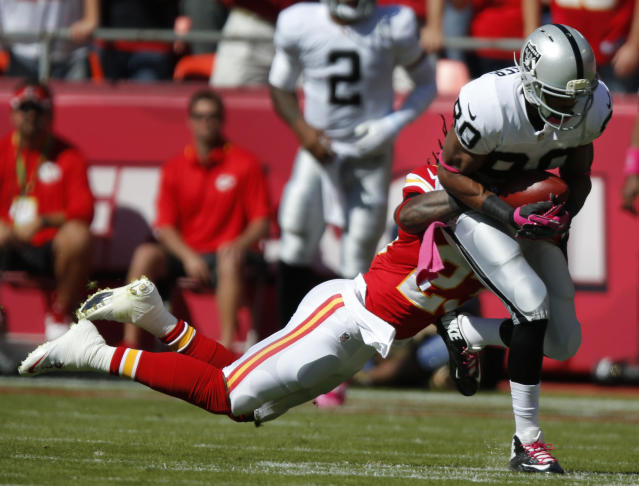 Oakland Raiders wide receiver Rod Streater (80) is tackled by Kansas City Chiefs free safety Kendrick Lewis (23) during the first half of an NFL football game at Arrowhead Stadium in Kansas City, Mo., Sunday, Oct. 13, 2013. (AP Photo/Ed Zurga)