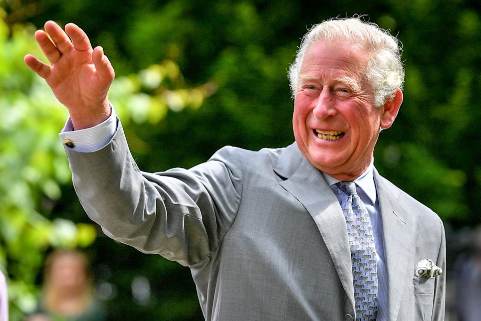 The Prince of Wales gestures to crowds of hospital staff watching from a distance as he chats with front line key workers who who have responded to the COVID-19 pandemic during a visit to Gloucestershire Royal Hospital.