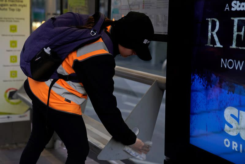 An essential worker sanitises a tram stop under COVID-19 lockdown restrictions in Melbourne