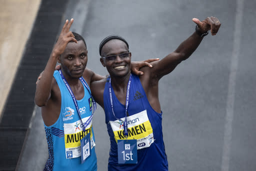 John Kipkorir Komen, of Kenya, right, and Rwanda's Felicien Muhitira gesture after the 37th Athens Marathon on Sunday, Nov, 10, 2019. The 42-year-old Kenyan runner finished in a time of 2 hours, 16 minutes, 34 seconds, beating Rwanda's Felicien Muhitira, 17 years his junior, by nine seconds. (AP Photo/Yorgos Karahalis)