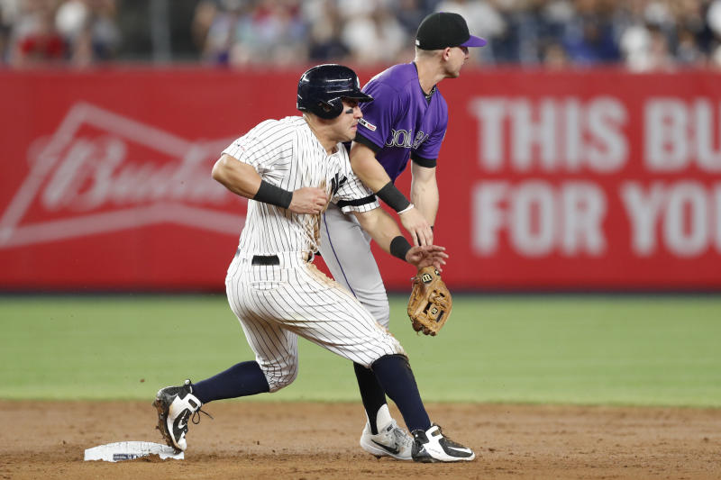 New York Yankees' Mike Tauchman, left, collides with Colorado Rockies second baseman Ryan McMahon as McMahon watches the throw from catcher Chris Ianetta roll into the outfield during the sixth inning of a baseball game, Friday, July 19, 2019, in New York. Tauchman reached third on the play. (AP Photo/Kathy Willens)