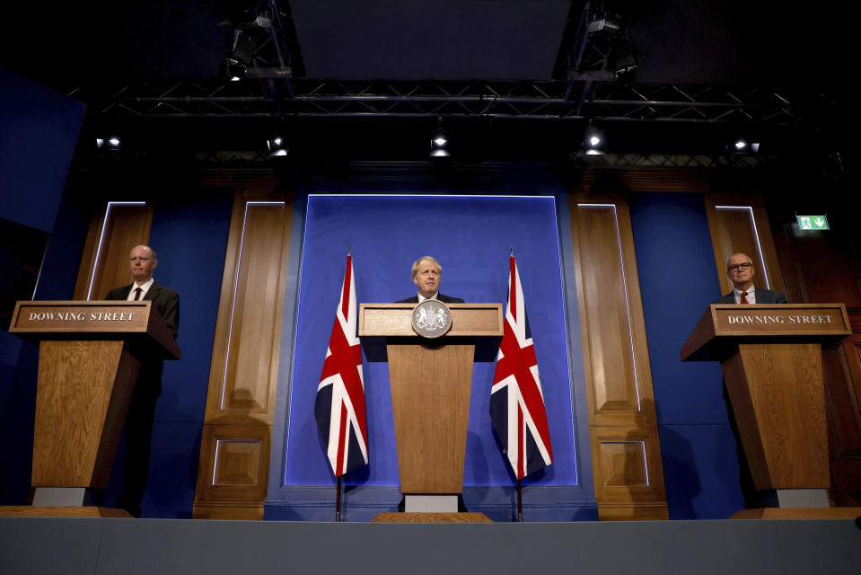 From left, Britain's Chief Medical Officer for England Chris Whitty, Prime Minister Boris Johnson and Chief Scientific Adviser Sir Patrick Vallance attend a media briefing in Downing Street, London, Tuesday, Sept. 14, 2021. An expert advisory panel has recommended the U.K. government offer a third dose of COVID-19 vaccine to everyone over age 50 to protect against the coronavirus. (Dan Kitwood/Pool Photo via AP)