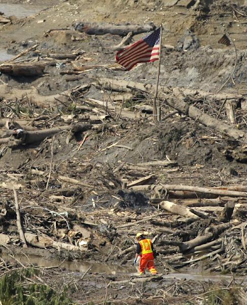 A search worker walks through a channel of water as a flag flies in the debris field Monday, March 31, 2014, near Darrington, Wash., at the site of the massive mudslide that hit the nearby community of Oso,Wash. on March 22, 2014. (AP Photo/Ted S. Warren)