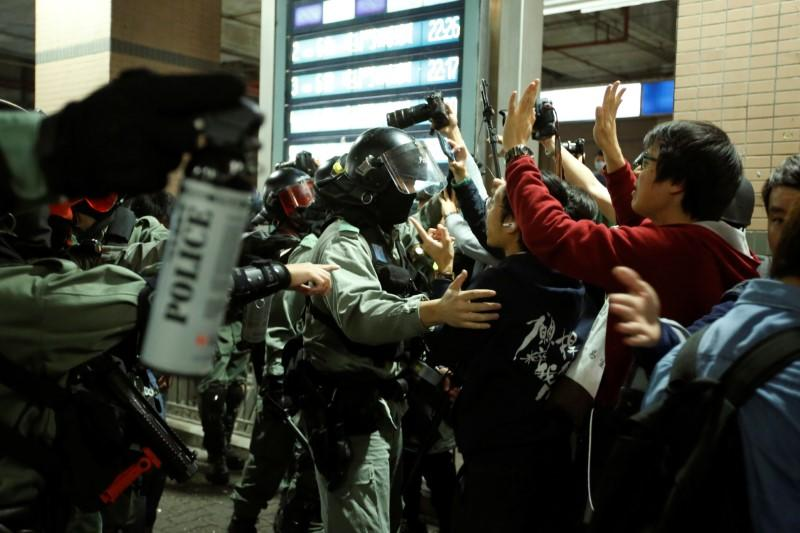 Police officers brandish pepper spray to disperse protesters who gathered at the site of an attack six months ago by an armed mob on anti-government demonstrators at the district of Yuen Long in Hong Kong