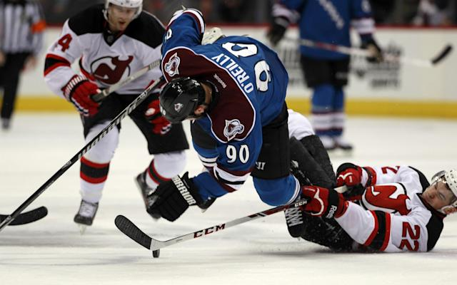 Colorado Avalanche center Ryan O'Reilly, center, is tripped by New Jersey Devils defenseman Adam Gelinas, right, as Devils center Adam Henrique covers in the second period of an NHL hockey game in Denver, Thursday, Jan. 16, 2014. (AP Photo/David Zalubowski)